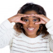 A closeup studio portrait of a young handsome, serious woman looking through her fingers like binoculars, searching for something — Stock Photo