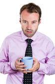 A close-up portrait of a very tired, almost falling asleep businessman holding a cup of coffee — Stockfoto
