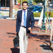 Stock Photo: Portrait of young smiling, happy, successful business man, executive walking outside down street holding briefcase