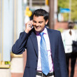 A closeup portrait of a young busy, happy, smiling business man talking on his phone while walking outside down the street holding a briefcase — Stock Photo #36388473