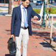 Stock Photo: Portrait of young smiling, happy, successful business man, executive walking outside down street holding briefcase, looking at wristwatch