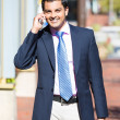 A closeup portrait of a young busy, happy, smiling business man talking on his phone while walking outside down the street holding a briefcase — Stock Photo #36389503