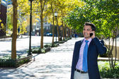 A closeup portrait of a young busy, happy, smiling business man talking on his phone while walking outside down the street holding a briefcase — Stock Photo