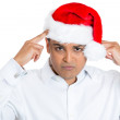 Closeup portrait of young worried stressed man in red santa claus hat with hands on head looking at you camera gesture — Stock Photo