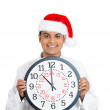 Closeup portrait of handsome successful smiling confident young man wearing red santa claus hat holding pink big clock in front of chest — Stock Photo