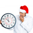 Closeup portrait of worried young man wearing red santa claus hat, hands in mouth holding clock — Stock Photo