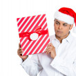 Closeup portrait of handsome young man in red santa claus hat carefully holding, shaking and listening to wrapped gift to figure out what it could be — Stock Photo #36474129