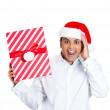 Closeup portrait of happy young handsome man in red santa claus hat looking surprised hands on cheek showing wrapped present — Stock Photo #36474137