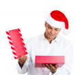 Closeup portrait of young man in red santa claus hat opening gift and very upset at what he received — Stock Photo