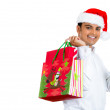 Closeup portrait of christmas shopping excited young handsome man, wearing red santa claus hat giving thumbs up and holding bag — Stock Photo
