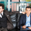Closeup portrait of two businessman sitting on black couch waiting to talk someone important or an office appointment or interview. One guy is bored. Other is pissed off. — Stock Photo