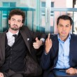 Closeup portrait of two co-workers, businessmen, corporate or government employees sitting on black couch, one giving middle finger, other thumbs up sign — Stock Photo #36599217