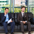 Closeup portrait of two bored businessman sitting on black couch applying and interviewing for a job, one guy has pen to mouth as mustache, other is daydreaming — Stock Photo