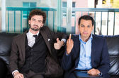 Closeup portrait of two co-workers, businessmen, corporate or government employees sitting on black couch, one giving middle finger, other thumbs up sign — Stock Photo
