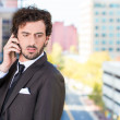 Closeup portrait of a handsome young, serious business man talking on a cell phone outside on a balcony of his apartment — Stock Photo