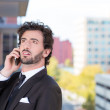 Closeup portrait of a handsome young, happy business man talking on a cell phone relaxed on a balcony of his apartment isolated on a city background — Foto Stock
