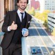 Closeup portrait of good looking smiling, happy businessman giving you a thumbs up, enjoying a drink, standing on his balcony — Foto Stock
