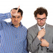 A portrait of two businessmen: a bully standing upfront showing a looser sign and a nerd, shy guy wearing glasses standing behind him — Stock Photo
