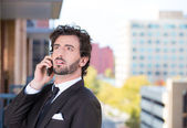 Closeup portrait of a handsome young, happy business man talking on a cell phone relaxed on a balcony of his apartment isolated on a city background — Stock Photo