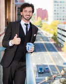 Closeup portrait of good looking smiling, happy businessman giving you a thumbs up, enjoying a drink, standing on his balcony — Stock Photo