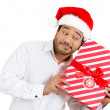 Closeup portrait of handsome young man in red santa claus hat carefully holding, shaking and listening to wrapped gift to figure out what it could be — Stock Photo #36727571