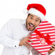 Closeup portrait of handsome young man in red santa claus hat carefully holding, shaking and listening to wrapped gift to figure out what it could be — Stock Photo