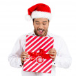 Closeup portrait of happy young handsome man in red santa claus hat looking surprised hands on gift showing wrapped present — Stock Photo #36727589