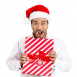 Closeup portrait of happy young handsome man in red santa claus hat looking surprised hands on gift showing wrapped present — Stock Photo