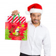 Closeup portrait of shopping smiling excited young handsome man wearing red santa claus hat holding, pointing showing a festive bag — Stock Photo