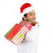 Closeup portrait of christmas shopping excited young handsome man, wearing red santa claus hat holding bag — Stock Photo