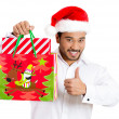 Closeup portrait of christmas shopping excited young handsome man, wearing red santa claus hat holding bag giving thumbs up — Stock Photo