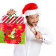 Closeup portrait of shopping smiling excited young handsome man wearing red santa claus hat holding a,festive bag and showing a peace or two sign — Stock Photo