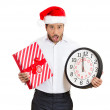 Closeup portrait of worried young man wearing red santa claus hat, holding clock and gift in hands — Stock Photo #36727613