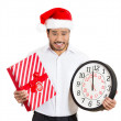 Closeup portrait of worried young man wearing red santa claus hat, holding clock and gift in hands — Stock Photo