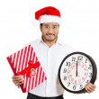 Closeup portrait of worried young man wearing red santa claus hat, holding clock and gift in hands — Stock Photo #36727635