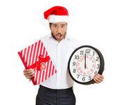 時計、ギフトの手で保持している赤いサンタ クロースの帽子を着て心配の若い男のクローズ アップの肖像画 — ストック写真