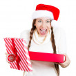 Closeup portrait of a young beautiful excited woman wearing red santa claus hat, opening gift box and super happy at what she gets — Stock Photo