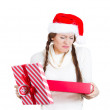 Closeup portrait of young woman in red santa claus hat opening gift, very upset at what she received — Stock Photo