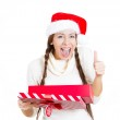 Closeup portrait of a beautiful Christmas girl wearing red Santa hat, holding opened gift box, giving thumb up, happy with the present she received — Stock Photo #36851821