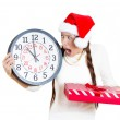 Closeup portrait of worried, stressed, in a hurry young woman wearing red santa claus hat, holding clock, gift box — Stock Photo #36851831
