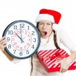 Closeup portrait of worried, stressed young woman wearing red santa claus hat, holding clock and a gift box — Stock Photo