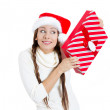 Santa girl holding new year gift. Young beautiful excited, happy woman in red hat looking sideways showing Christmas present — Stock Photo
