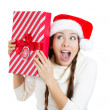 Santa girl holding new year gift. Young beautiful excited, happy woman in red santa hat looking sideways showing Christmas present — Stock Photo