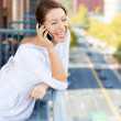 Closeup portrait of a beautiful, happy woman talking on a cell phone relaxed on a balcony of her apartment — Stock Photo