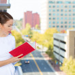 Closeup portrait of beautiful, young, happy, relaxed woman enjoying a weekend on sunny day, on balcony of her apartment, reading a book — Stock Photo