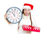 Closeup portrait of beautiful, young happy woman wearing red santa claus hat, holding gift box, wall clock, running on time — Stock Photo