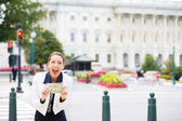 Closeup portrait of happy, excited corrupt politician in washington dc, holding dollar bills isolated on Capitol building background — Stock Photo