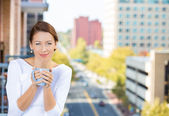 Closeup portrait of beautiful, happy, relaxed woman holding a cup of coffee, enjoying a weekend on sunny day, on balcony of her apartment — Stock Photo