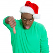 Closeup portrait of mean young man in red santa claus hat with thumbs down at you camera gesture — Stock Photo