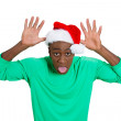 Closeup portrait of mean young man in red santa claus hat placing thumbs on head sticking tongue out at camera gesture — Stock Photo